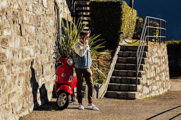 Bel giovane con il telefono cellulare in piedi vicino alla moto rossa in città e parlare.