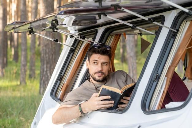Bel giovane con libro aperto seduto alla finestra della casa su ruote