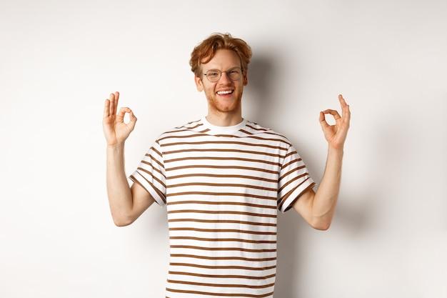 Bel giovane con i capelli rossi disordinati e gli occhiali sorridenti, mostrando segni ok in approvazione, lodando qualcosa, consigliando un buon prodotto, sfondo bianco.