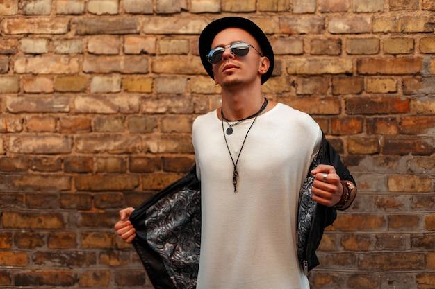 Bel giovane con occhiali da sole in un cappello nero e giacca di pelle nera in posa vicino al muro di mattoni