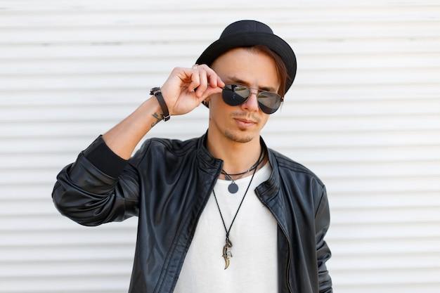 Bel giovane con occhiali da sole in una giacca di pelle nera con magliette bianche vicino al muro di metallo bianco