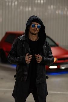 Bel giovane con occhiali da sole blu alla moda in elegante giacca di pelle con felpa con cappuccio alla moda vicino a un'auto rossa per strada di notte