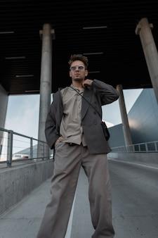 Bel giovane con occhiali da sole vintage in elegante abito grigio oversize con borsa vicino a un edificio moderno