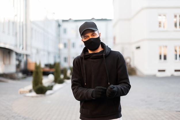 Bel giovane modello con maschera medica protettiva e berretto elegante in felpa nera alla moda e guanti in città. stile urbano moderno maschile e pandemia