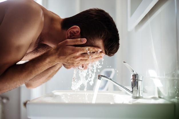 Bel giovane uomo nudo si lava la faccia in bagno a casa.