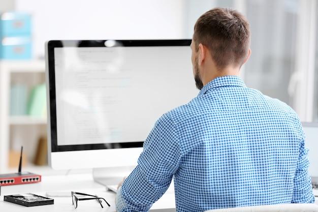Bel giovane programmatore che lavora in ufficio