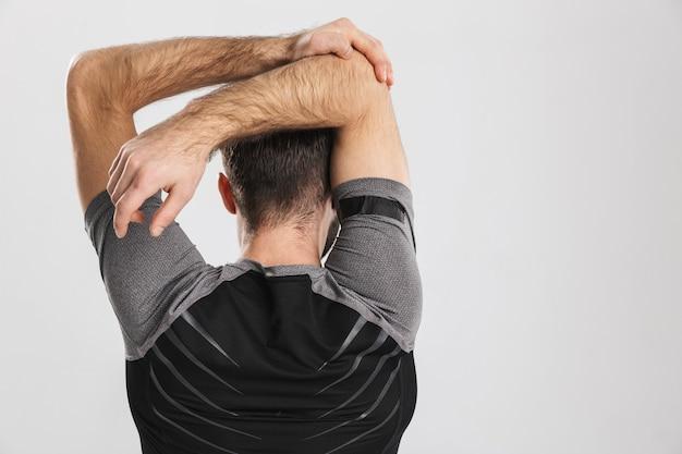 Bel giovane sportivo fitness uomo in posa, fare esercizi di stretching.