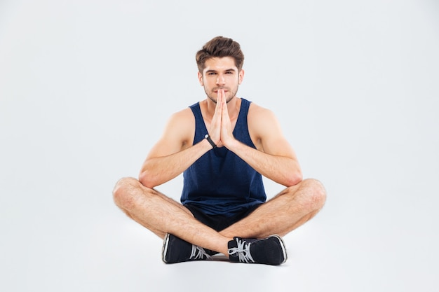 Bel giovane sportivo seduto e facendo yoga su sfondo bianco