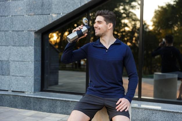 Bel giovane sportivo acqua potabile da una bottiglia all'aperto