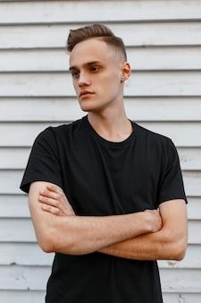 Bel giovane uomo alla moda con un'acconciatura alla moda in una t-shirt nera alla moda in posa
