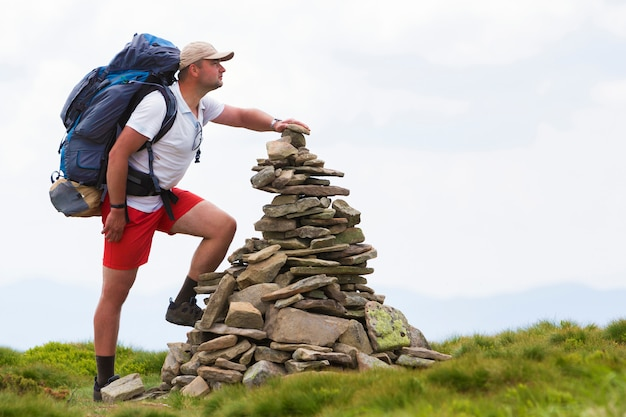 Giovane uomo turistico bello con lo zaino che fa il mucchio della piramide delle pietre accese dall'erba verde del sole luminoso di estate. turismo, viaggi e concetto di punto di riferimento.