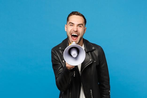 Bel giovane uomo con la barba lunga in giacca nera t-shirt bianca urlare nel megafono, annuncia la vendita di sconti isolata sul ritratto in studio di sfondo muro blu. concetto di stile di vita della gente. mock up copia spazio.