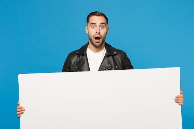 Bel giovane uomo con la barba lunga tenere un grande cartellone bianco vuoto vuoto per contenuti promozionali isolato su sfondo blu muro ritratto in studio. concetto di stile di vita di persone sincere emozioni. mock up copia spazio