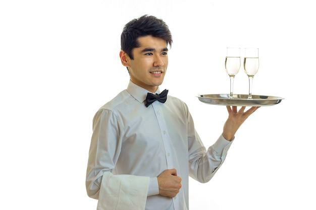Bel giovane cameriere sorridente e in possesso di un bicchieri di champagne su un vassoio che è isolato su un muro bianco