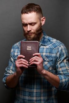 Uomo di handsone che legge e che prega sopra la bibbia in una stanza buia sopra struttura grigia