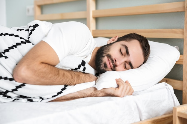 Uomo sorridente di handsonme che dorme su un cuscino nel letto