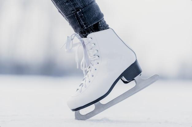 Fare la verticale sulla punta dei pattini da ghiaccio su un lago invernale ghiacciato