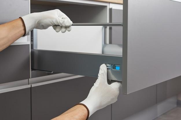 Tuttofare che monta e installa un cassetto in cucina. il lavoratore fissa il meccanismo del mobile del cassetto dell'armadio.