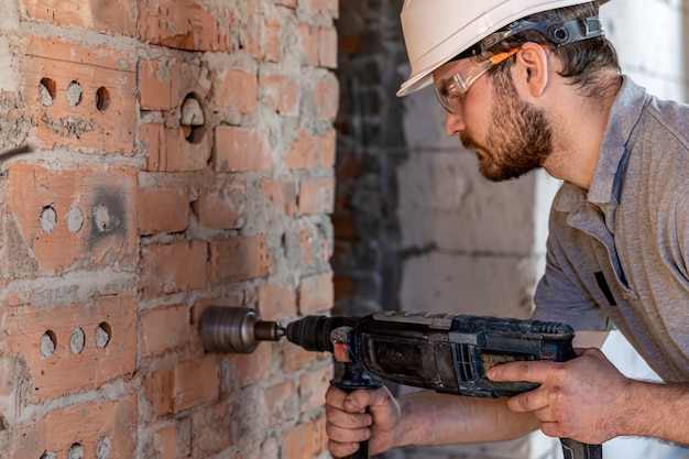 Tuttofare in un cantiere nel processo di perforazione di un muro con un perforatore.