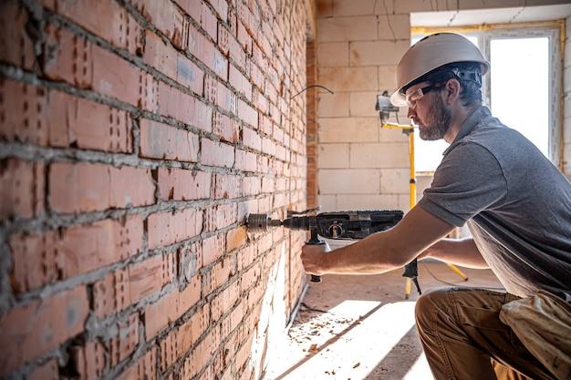 Tuttofare in un cantiere in procinto di perforare un muro con un perforatore