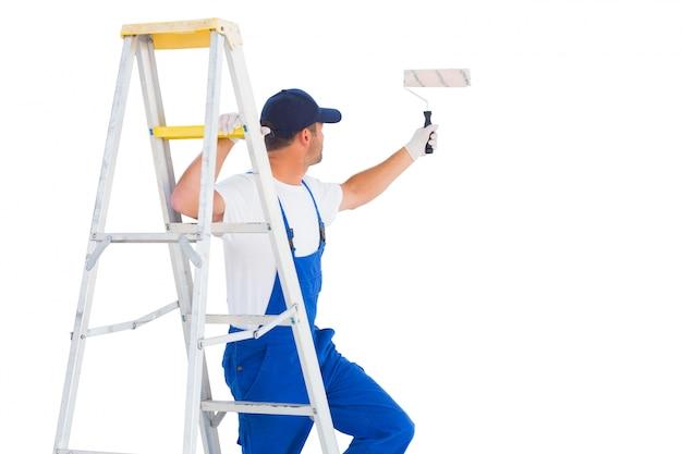 Tuttofare sulla scala mentre si utilizza il rullo di vernice