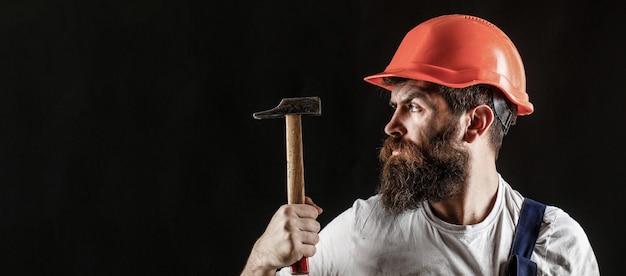 Servizi di tuttofare. industria, tecnologia, uomo costruttore, concetto. operaio barbuto con barba, casco da costruzione, elmetto. martellare a martello. costruttore in casco, martello, costruttori tuttofare in elmetto protettivo