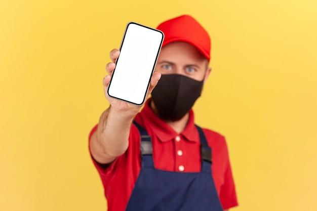 Tuttofare che mostra lo smartphone con display vuoto alla fotocamera, riparatore che chiama l'applicazione online