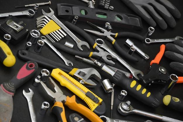 Kit di attrezzi tuttofare sul tavolo di legno nero. molte chiavi e cacciaviti, pilette e altri strumenti per qualsiasi tipo di riparazione o lavori di costruzione. set di strumenti riparatore