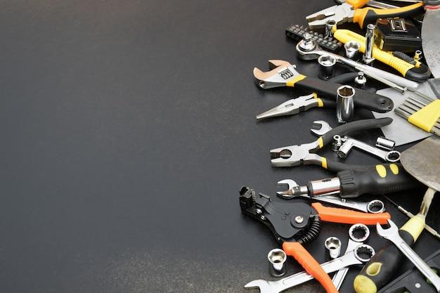 Kit di attrezzi tuttofare sul tavolo di legno nero. molte chiavi e cacciaviti, pilette e altri strumenti per qualsiasi tipo di riparazione o lavori di costruzione.