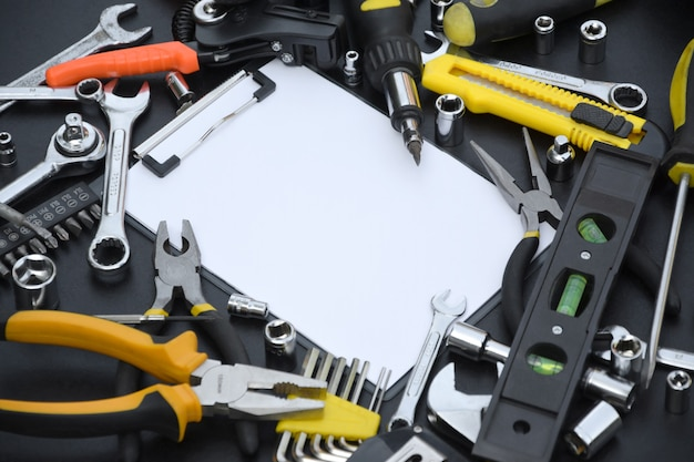 Kit di attrezzi tuttofare sulla tavola di legno nera con lo spazio della copia nella compressa di carta bianca
