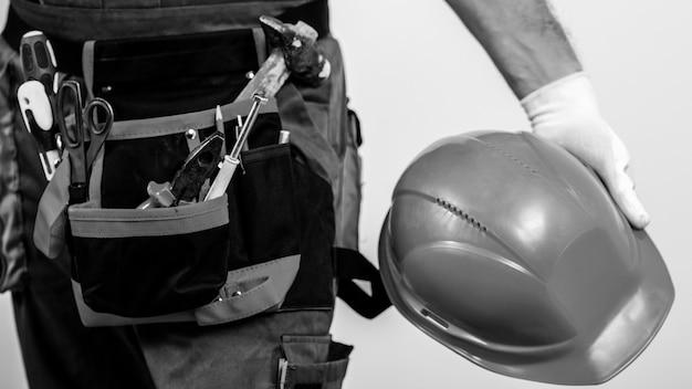 Tuttofare con una cintura degli attrezzi. servizio di ristrutturazione della casa. operaio edile con strumenti e casco di sicurezza.