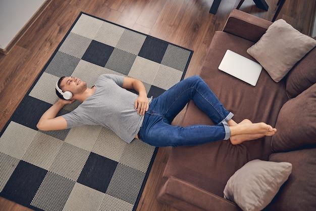 Hanfsome giovane maschio che rimane da solo sul pavimento con le gambe sul divano mentre si gode il tempo in cuffia