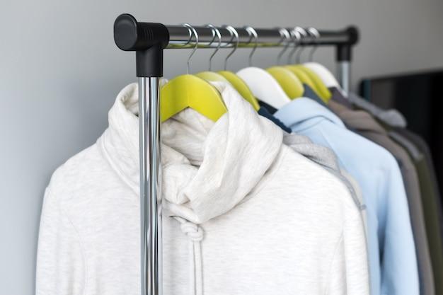 Supporto appendiabiti con vestiti caldi primaverili o autunnali su grigio