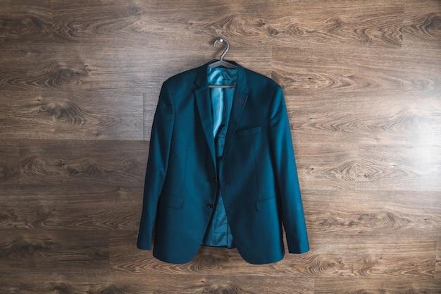 Appendiabiti con blazer blu sulla parete in legno marrone