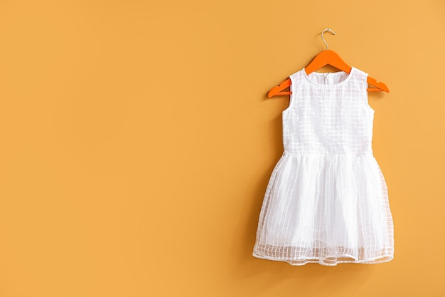 Appendiabiti con abito sulla parete arancione con copia spazio