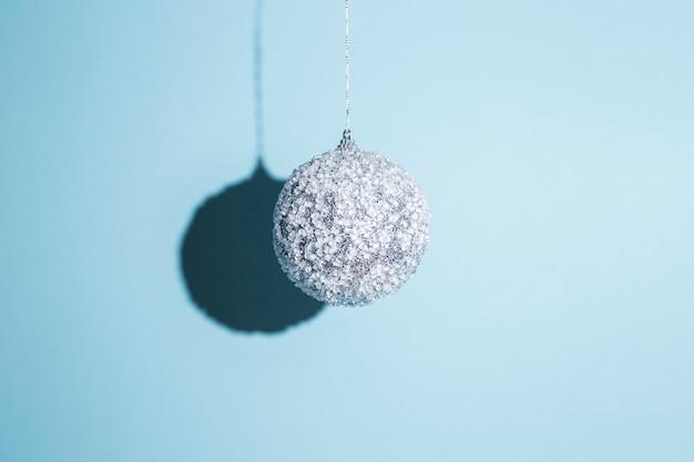 Palla di natale appesa su sfondo blu. luce forte.
