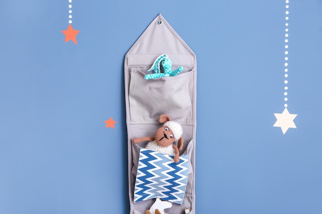 Organizer in tessuto da appendere con giocattoli per bambini su superficie colorata