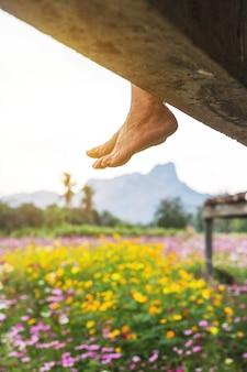 Appendere i piedi dell'uomo rilassante nel giardino di fiori colorati. prendere una pausa