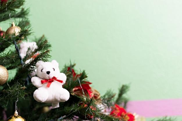 Un orsacchiotto bianco appeso che decora l'albero di natale