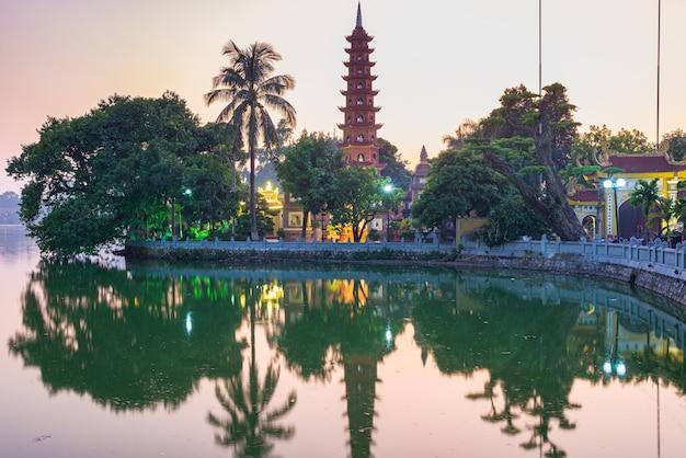 Pagoda buddista di hanoi (tran quoc pagoda) sul lago ad ovest di hanoi, tramonto, tempio illuminato, riflessione dell'acqua. vietnam