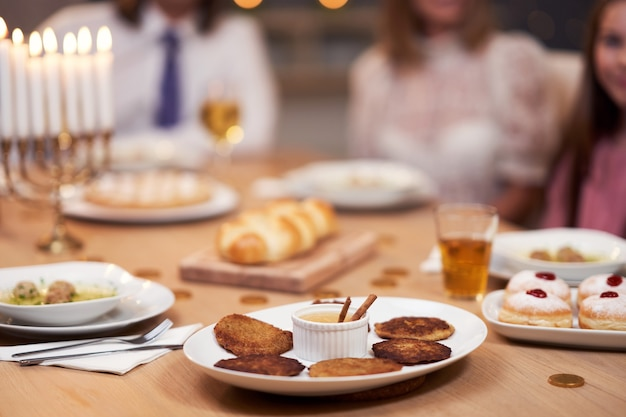Cena di hanukkah. famiglia riunita intorno alla tavola con i piatti della tradizione