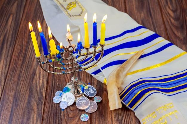 Festa di hanukkah sufganiyot con menorah sul tavolo di legno sullo sfondo della finestra