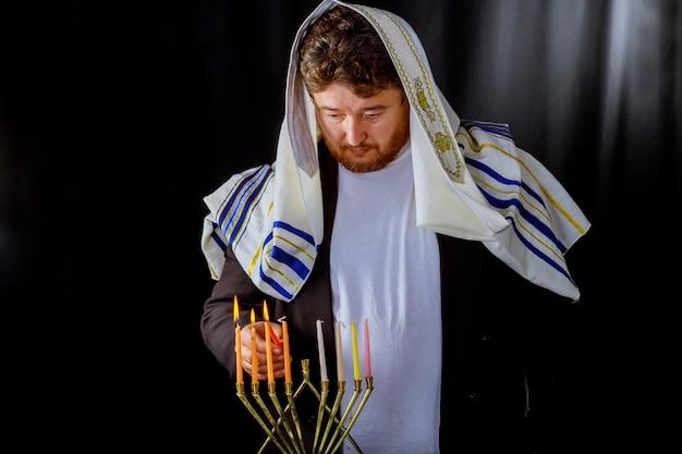 Candele ebraiche di celebrazione di hanukkah che bruciano nel menorah, uomo nei precedenti.