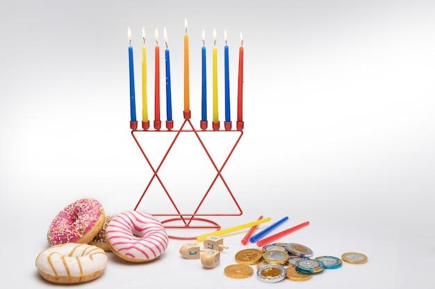 Scena di hanukkah, candele menorah, ciambelle, monete di cioccolato, dreidel.