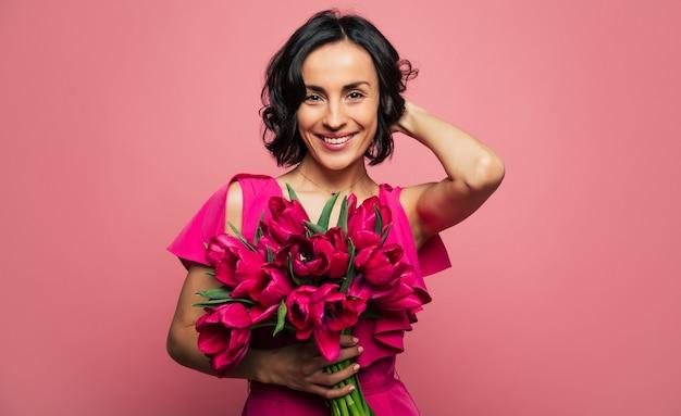 La donna più felice di sempre. foto ravvicinata di una ragazza bruna con un bel sorriso, che guarda nella telecamera e tiene un mazzo di tulipani nella mano destra.