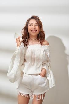 Ragazza asiatica di felicità che ascolta la musica dallo smartphone con gli auricolari che indossano abiti casual