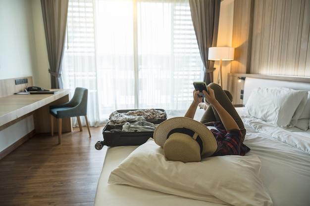 Felicità asiatica donna viaggiatore che dorme e utilizza il telefono cellulare intelligente sul letto in camera da letto di hotel o ostello durante il viaggio