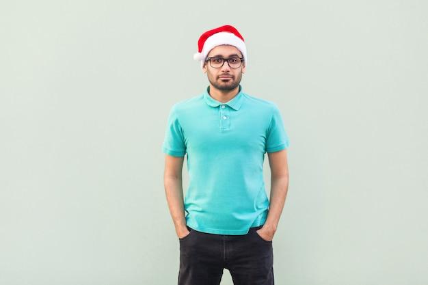 Felicità uomo barbuto con cappello rosso di natale e occhiali neri in piedi vicino al muro grigio e che guarda l'obbiettivo. foto in studio