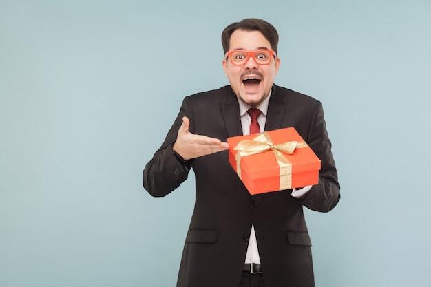 Uomo d'affari di felicità che tiene una scatola regalo rossa