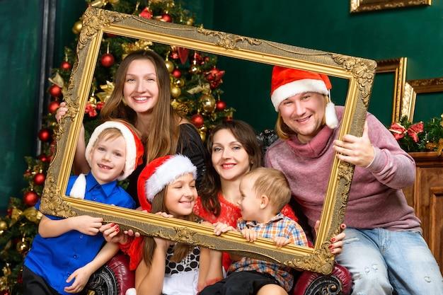 Concetto di famiglia di natale di felicità - grande casa sorridente della famiglia in cappelli dell'assistente di santa